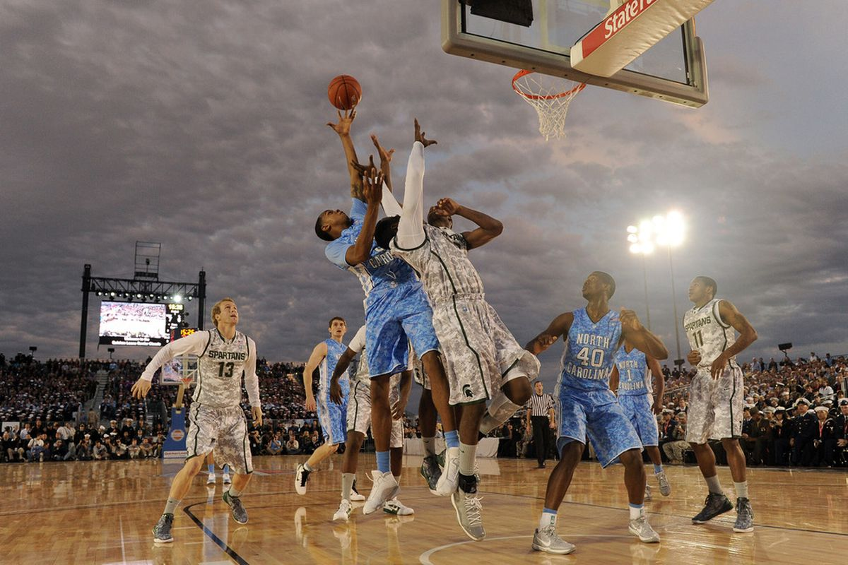 John Henson and Draymond Green grab a rebound during the Quicken Loans Carrier Classic.