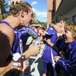 Wayne High School principal Mary Bray, right, celebrates with the boys cross-country team members as they find out they won the the 1A State Cross-Country Championships at Sugar House Park and Highland High School in Salt Lake City on Wednesday, Oct. 23, 2019.
