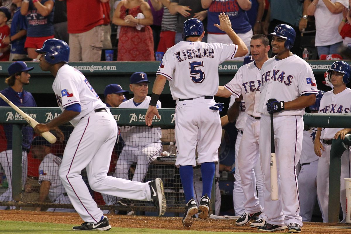 Aug 2, 2012; Arlington, TX, USA; Texas Rangers designated hitter Ian Kinsler (5) celebrates with his teammates after scoring in the seventh inning against the Los Angeles Angels at Rangers Ballpark.  Mandatory Credit: Matthew Emmons-US PRESSWIRE