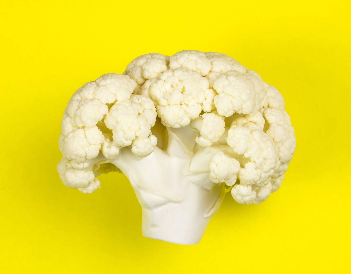 A single floret of cauliflower against a yellow background