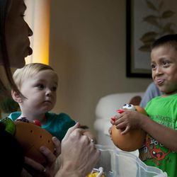 In this Thursday, Sept. 6, 2012 photo, Jessica Hooker, left, playfully sticks out her tongue as she plays with her adopted son Daniel, right, and daughter Ellyson, center, in Guatemala City. Daniel was 18 months old when the Tennessee couple Ryan and Jessica Hooker began the process to adopt him in Guatemala. They just got him at age 6. His is one of hundreds of adoption cases that were put in limbo five years ago, when the Guatemalan government declared a moratorium on international adoptions because of irregularities and fraud.