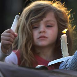 Addie Delisle lights her candle during a vigil for slain Police chief Michael Maloney, Friday, April 13, 2012 in Greenland, N.H. Maloney was trying to serve a search warrant Thursday night when a suspect opened fire, killing the 48-year-old chief, injuring four officers from other departments, and plunging the southeastern New Hampshire community of Greenland into a grief that residents say they won't soon get over.