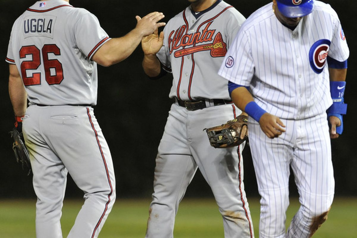 Dan Uggla of the Atlanta Braves and Alex Gonzalez celebrate the Braves victory against the Chicago Cubs at Wrigley Field in Chicago, Illinois. The Braves defeated the Cubs 3-0.  (Photo by David Banks/Getty Images)