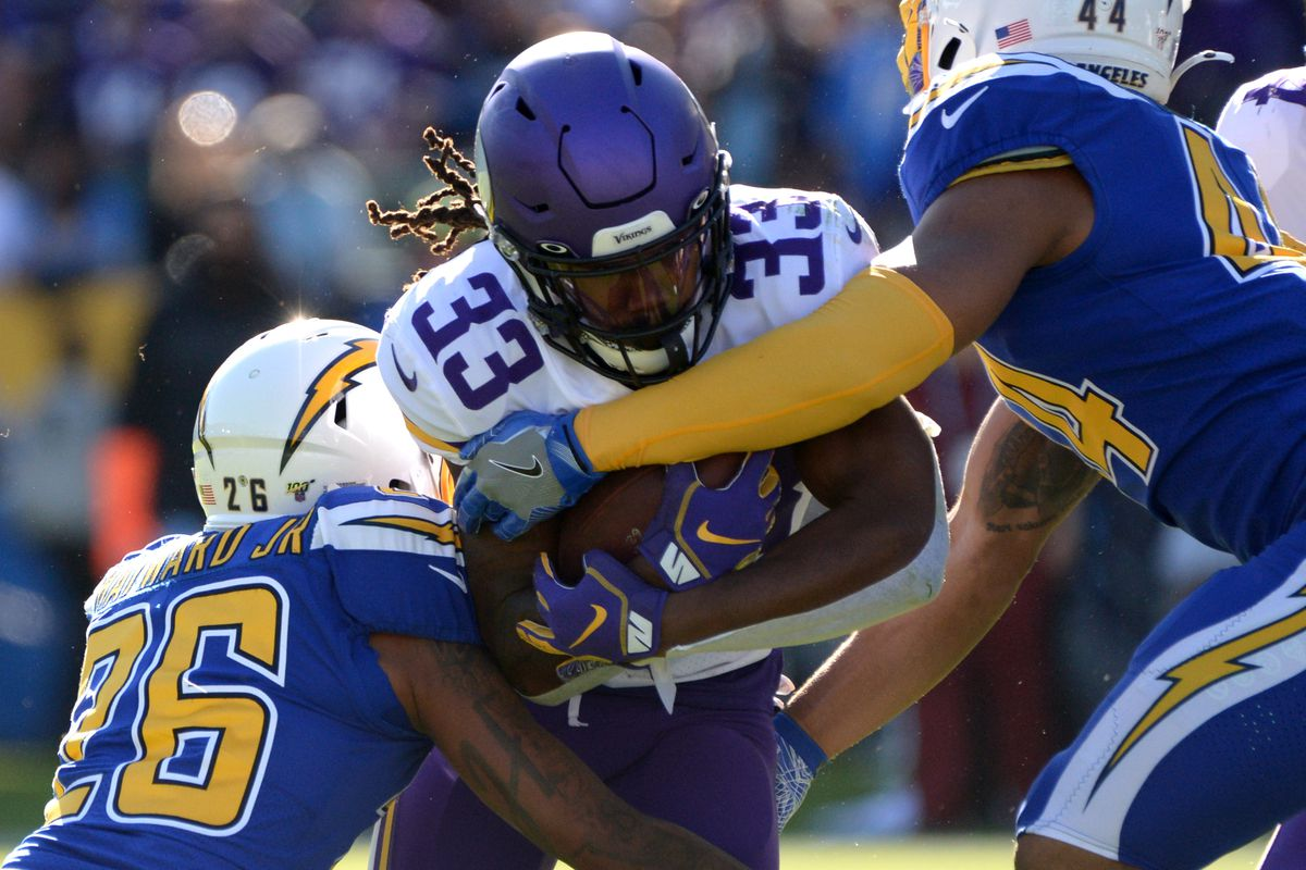 Minnesota Vikings running back Dalvin Cook is defended by Los Angeles Chargers cornerback Casey Hayward and outside linebacker Kyzir White during the first quarter at Dignity Health Sports Park.