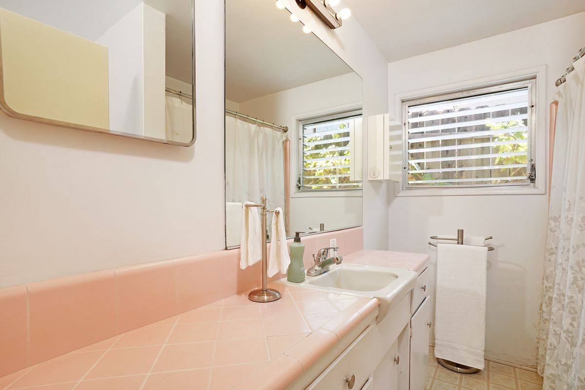 A bathroom with white walls and pink tile counters.
