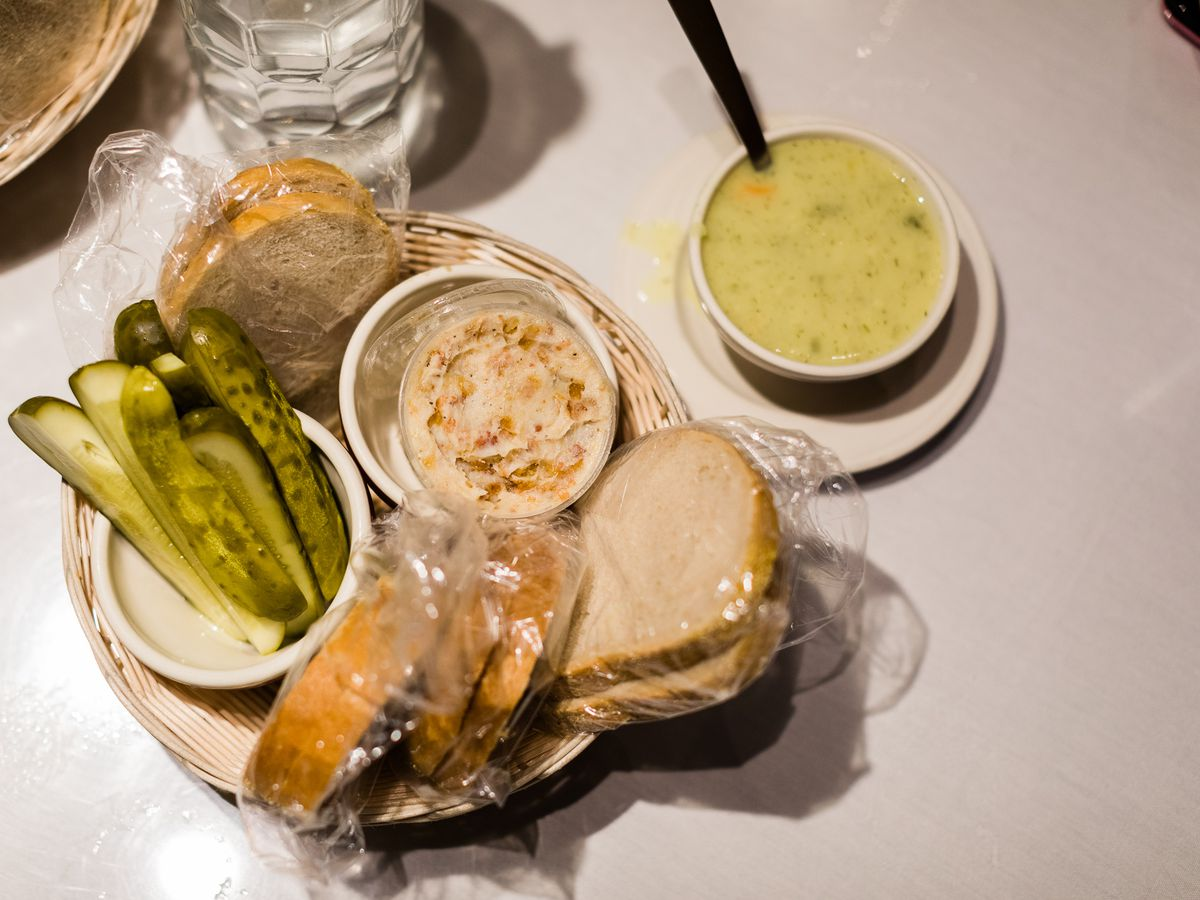 a plate with bacon spread, bread and pickles and a cup of yellow-colored dill pickle soup with a spoon in it