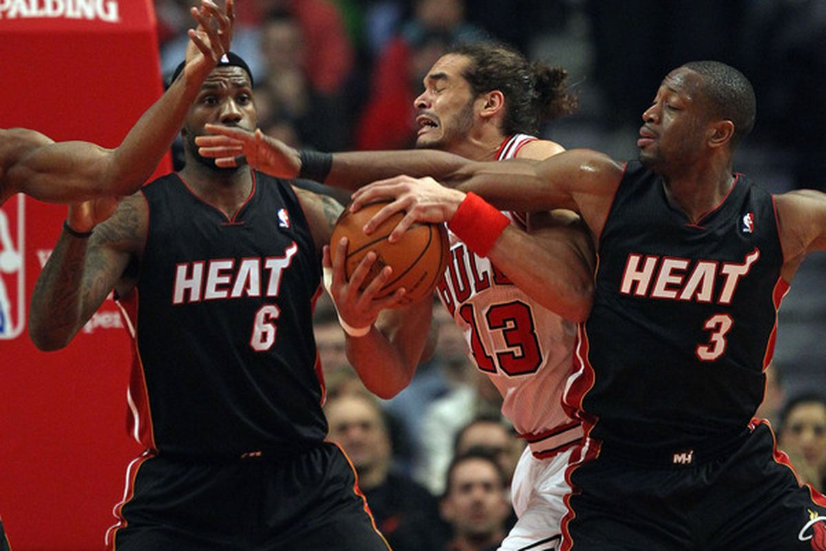 Joakim Noah of the Chicago Bulls battles for control of the ball with LeBron James and Dwyane Wade of the Miami Heat at the United Center on February 24 2011 in Chicago Illinois. (Photo by Jonathan Daniel/Getty Images)
