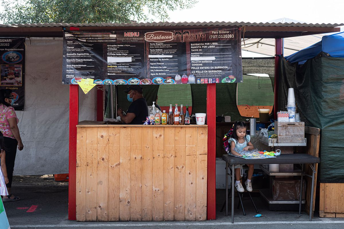 The stand of Barbacoa Mejia at the Richmond Pulga with a small child sitting in front.