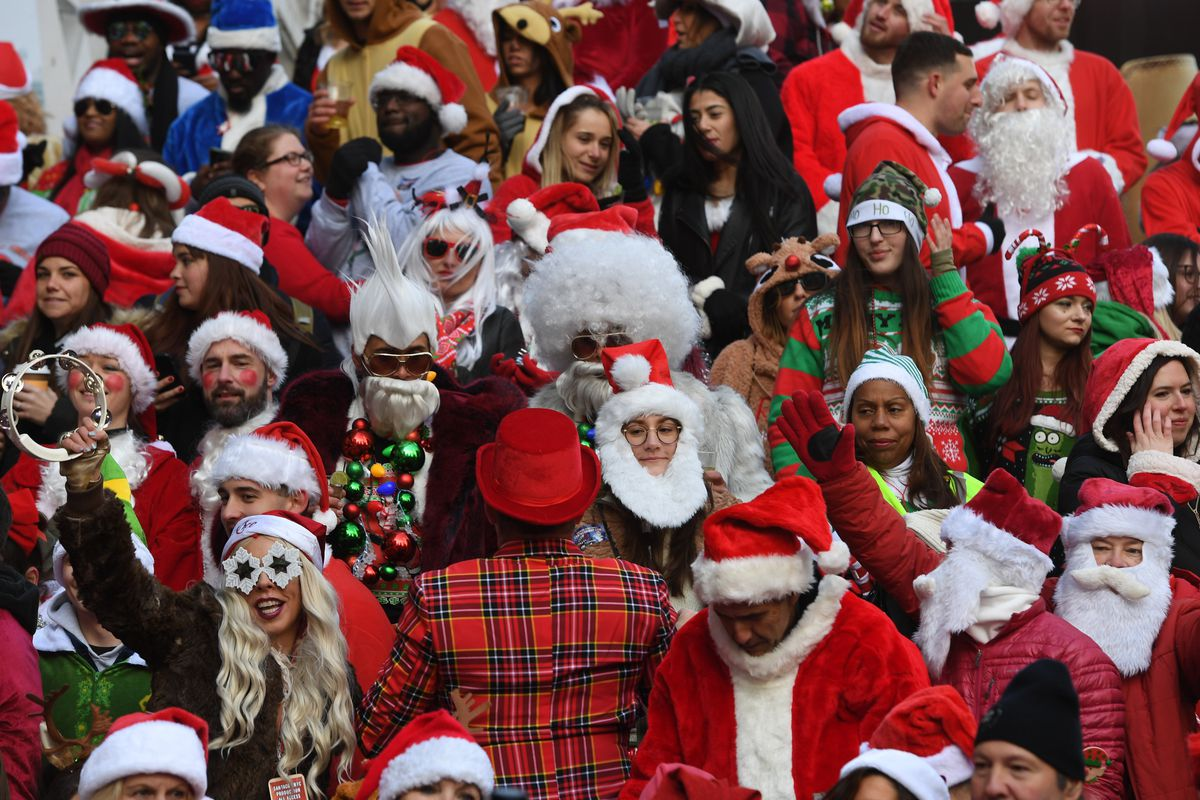 A group of people dressed as santa claus all crowded together on a new york city street.