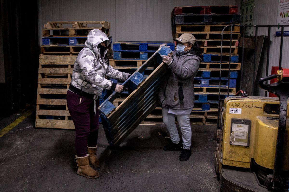 Two street vendors move a pallet inside a warehouse