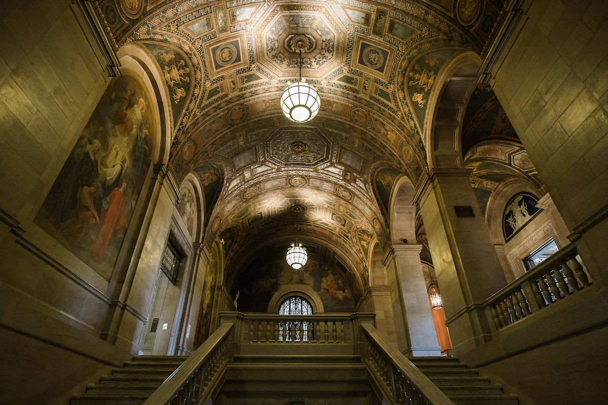 The interior of the Detroit Public Library. There is a large staircase leading to an upper level. The ceiling is elaborately decorated with an intricate design. There are large paintings and archways on both sides of the staircase.