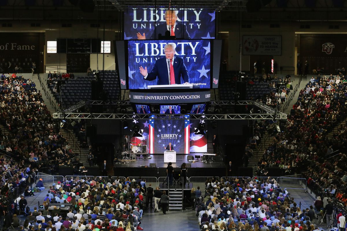 Donald Trump, speaking in a large campus center at Liberty University, with a large screen behind him projecting his image.