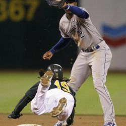 Kansas City Royals shortstop Alcides Escobar (2) waits to catch the ball before making the tag on Oakland Athletics' Jemile Weeks during the fifth inning of a baseball game Monday, April 9, 2012, in Oakland, Calif. Weeks was tagged out attempting to steal second base.