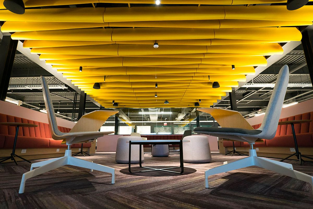 Futuristic meeting area with yellow panels on ceiling, dim lighting, mod chairs