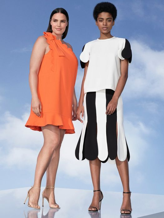 Two models one in orange dress and other in black and white top and skirt.
