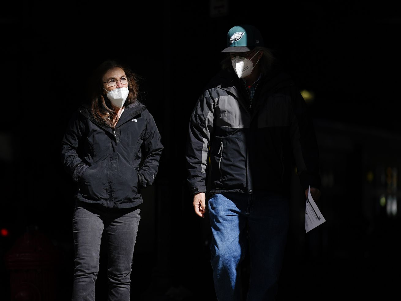 In this Wednesday, March 3, 2021 file photo, people wearing face masks as a precaution against the coronavirus walk through a shaft of light on a street in Philadelphia.