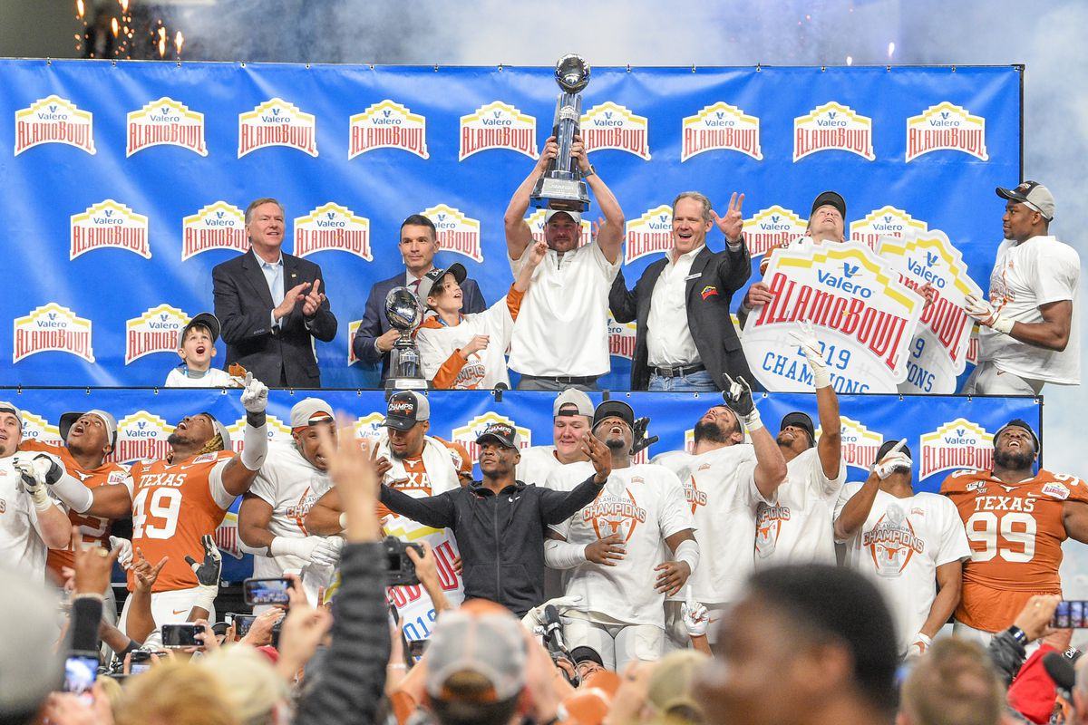Texas Longhorns head coach Tom Herman accepts the trophy for winning the Alamo Bowl football game between the Utah Utes and Texas Longhorns at the Alamodome on December 31, 2019 in San Antonio, TX.