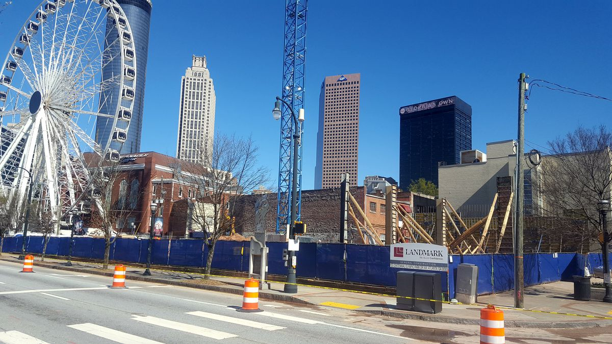 Construction fencing wraps around the project site, which houses a crane, and is next door to a Ferris wheel.