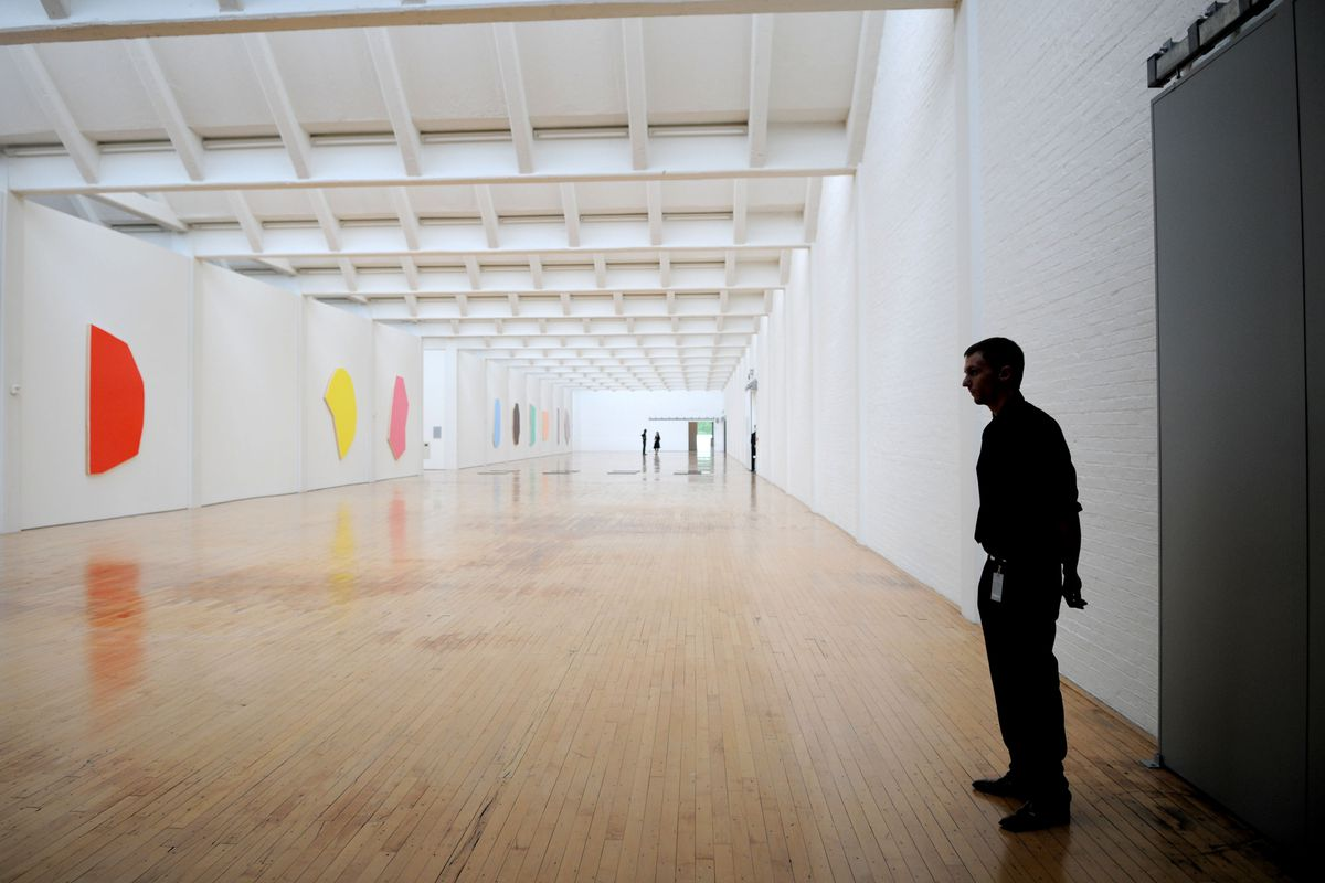 A large room with white walls. Colorful artwork hangs on the walls. There is a guard in the foreground standing against the wall.