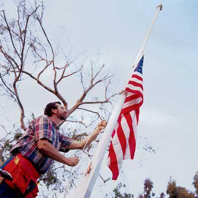 Man Raising American Flag On Flagpole