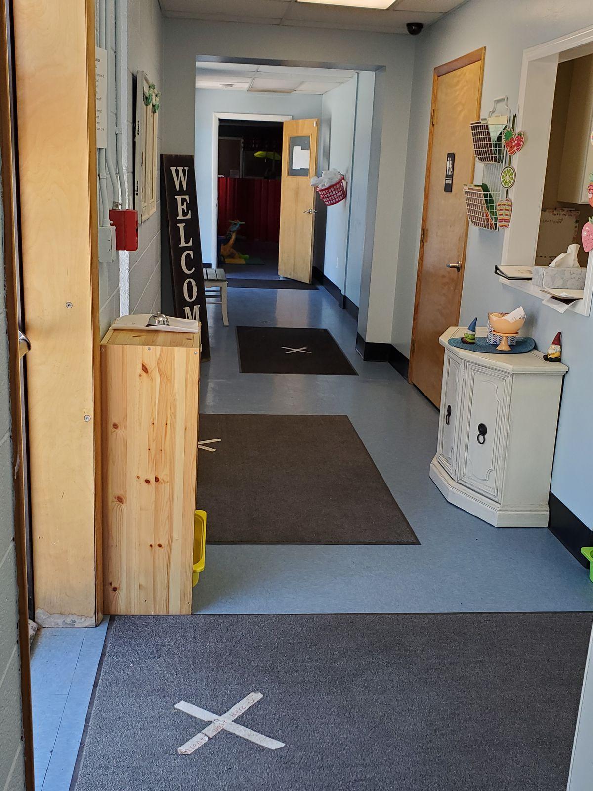 Xs taped in the entranceway of Li'l Graduates Child Development Center help prevent transmission of COVID-19 when children are dropped off.