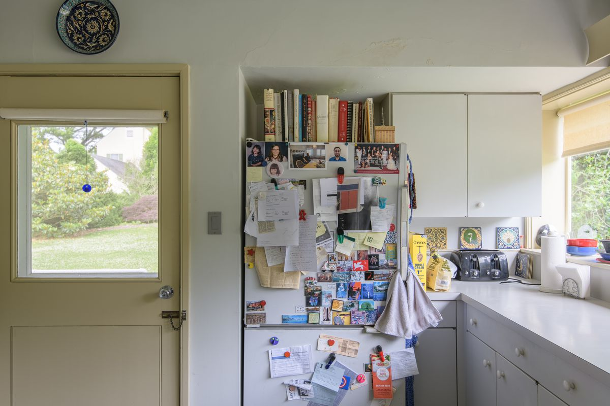 The kitchen in the Vanna Venturi house. There is a refrigerator that has many magnets and pieces of paper on its facade. On top of the refrigerator are a row of books. The kitchen walls and cabinetry are white. There is a door with a window looking out in