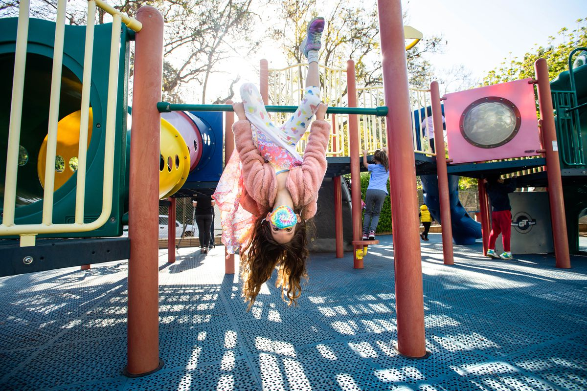 A masked kindergartner hangs upside down from playground equipment, her long hair dangling toward the ground.