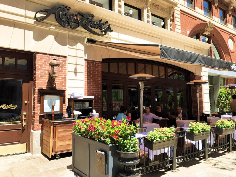 The sunny Boylston Street patio at Abe & Louie's, partially covered by an awning and surrounded by flower-filled planters.