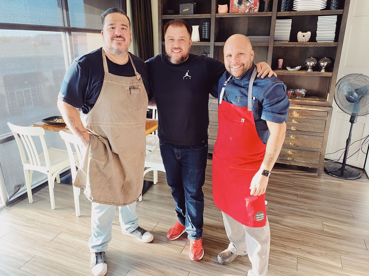 Three men wearing aprons with a bookcase behind them