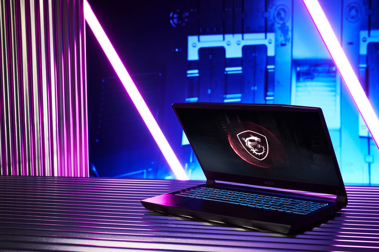 The MSI GL66 Pulse half open on a table, with black and purple lights in the background. The screen displays the MSI dragon-shield logo on a black background.