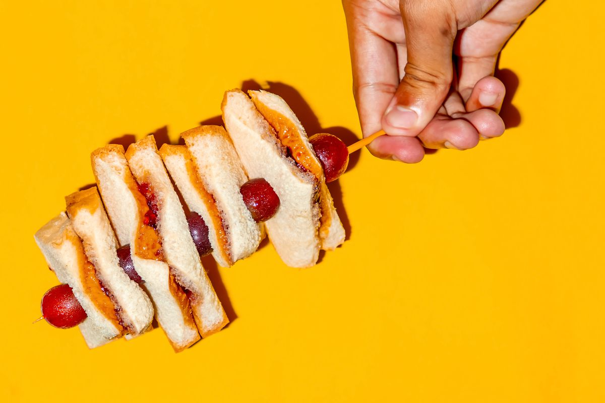 A hand holding a stack of PB & J sandwiches on a stick against a yellow background