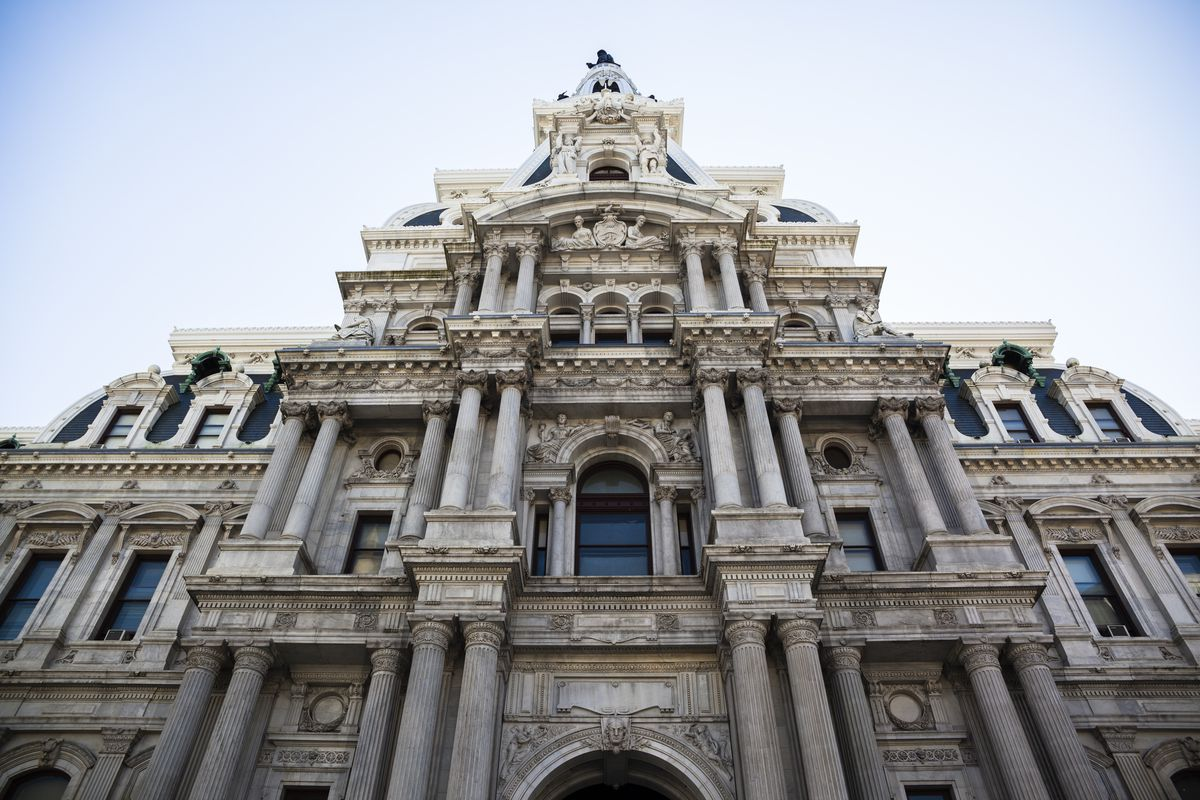 The exterior of Philadelphia City Hall. The facade is elaborately decorated with multiple columns and windows.