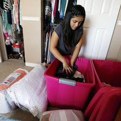 Stephanie Pesantes, who traveled to Washington, D.C., to meet with Michelle Obama, sorts clothing in Salt Lake City, Tuesday, July 28, 2015 as she prepares to go to college.