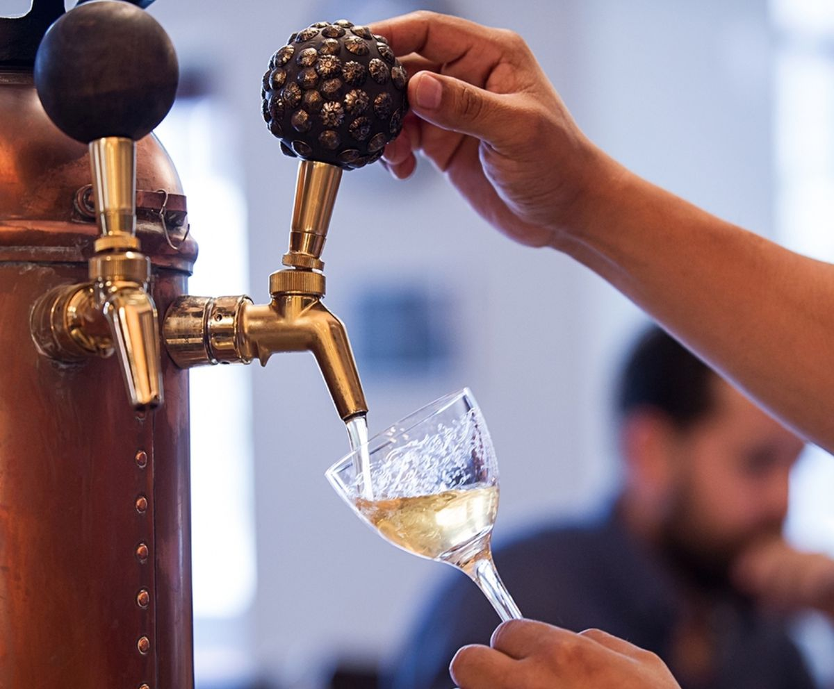 Hand pulling a tap that allows vermouth to pour out into a crystal glass.