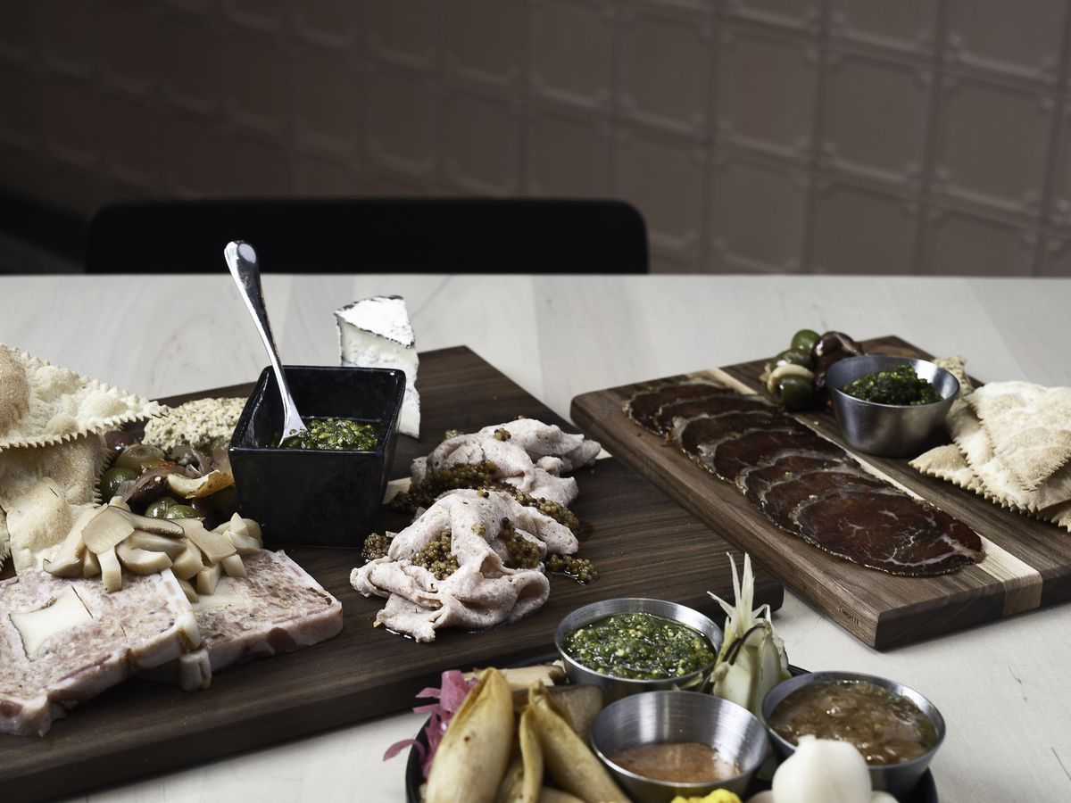 Boards of charcuterie, dips, and crackers, on a marble kitchen counter