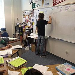 Students work together to answer questions through the critical thinking and inquiry process during tutorial groups in the AVID program being conducted at Granite Park Junior High School.