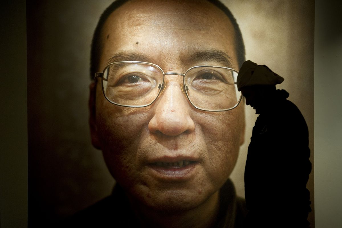 An image of Liu Xiaobo hangs on a wall and a silhouette of a man is in front of it.