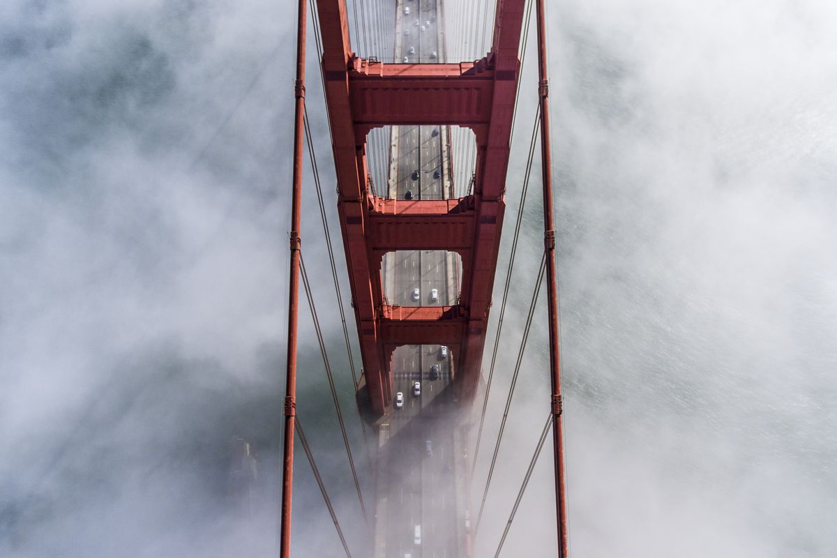 A photo from above one tower of the Golden Gate Bridge covered in fog.