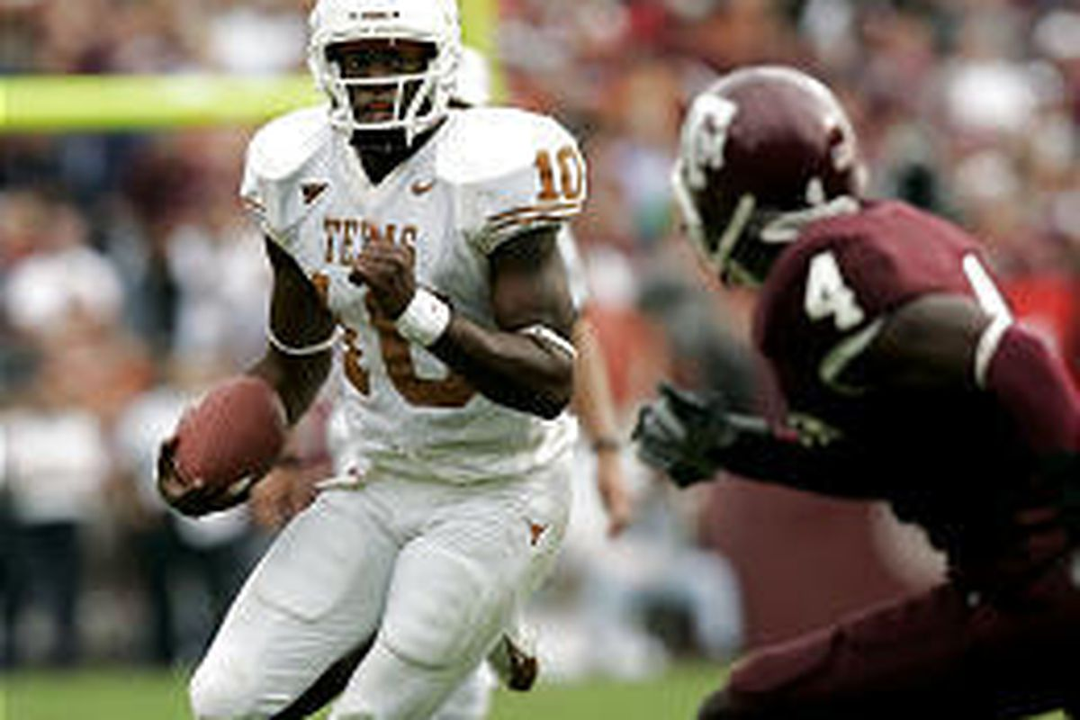 Texas quarterback Vince Young (10) looks upfield as he rushes for a gain Friday against Texas A\&M's Danny Garner in 40-29 victory.