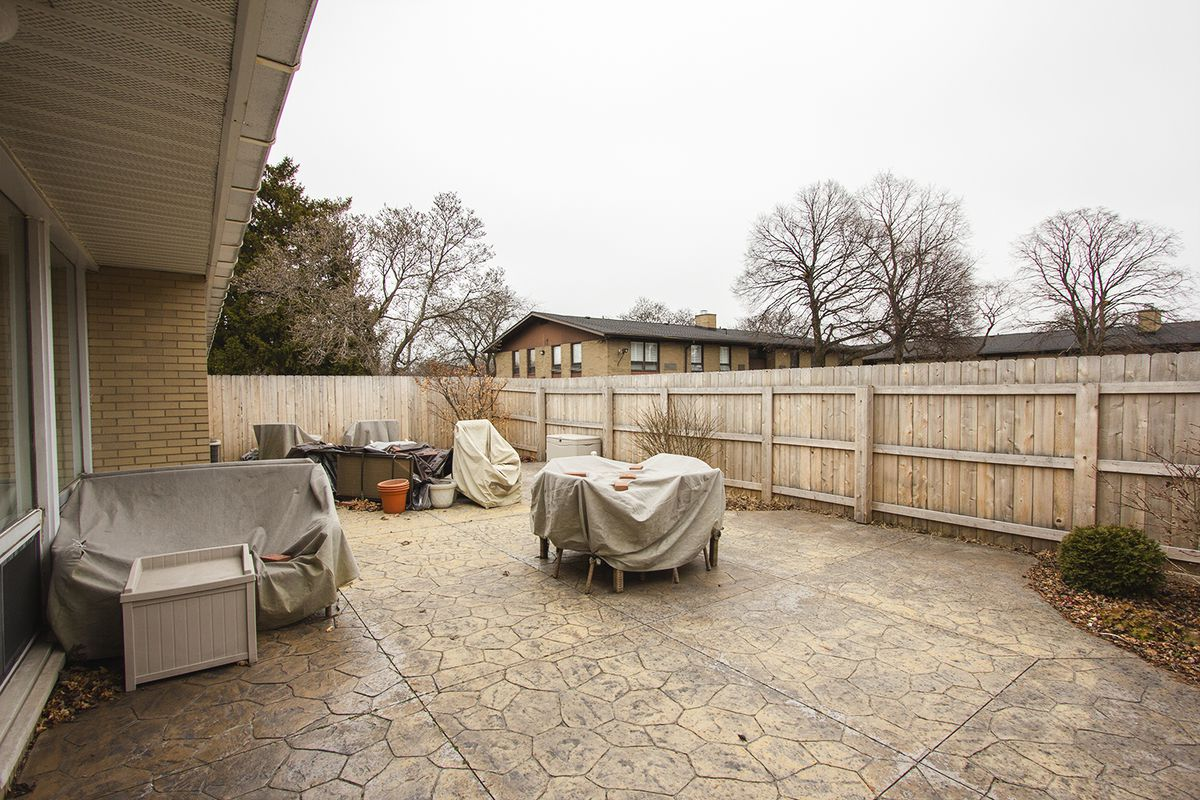 Back of the house has big slabs of tile with covered patio furniture.