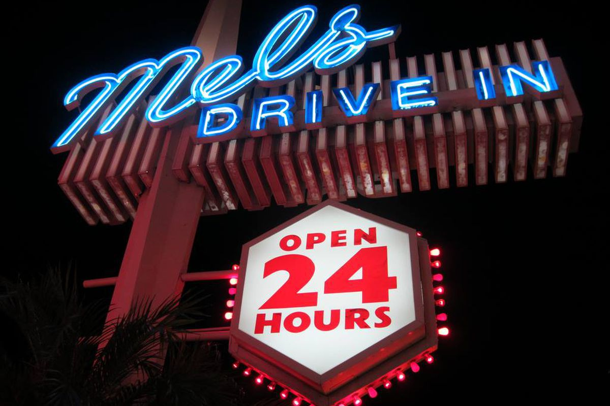 Mel's Drive-In sign glows with neon at night.