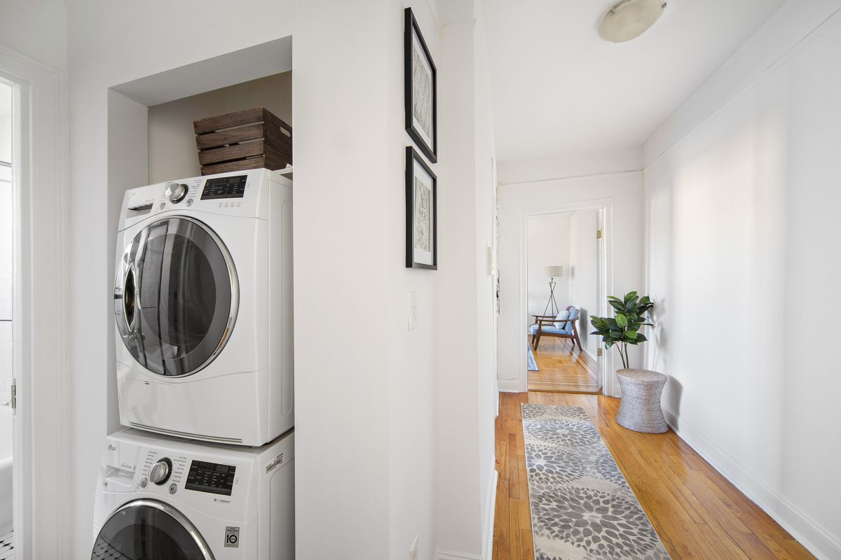 An in-unit washer/dryer next to a hallway.