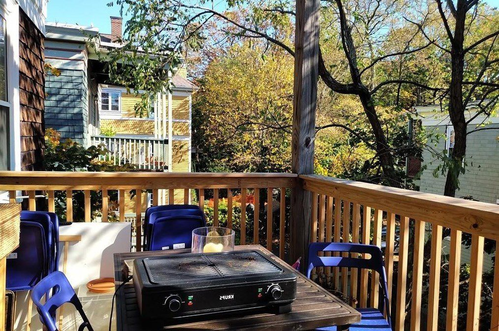 A small back deck with a table and chairs.