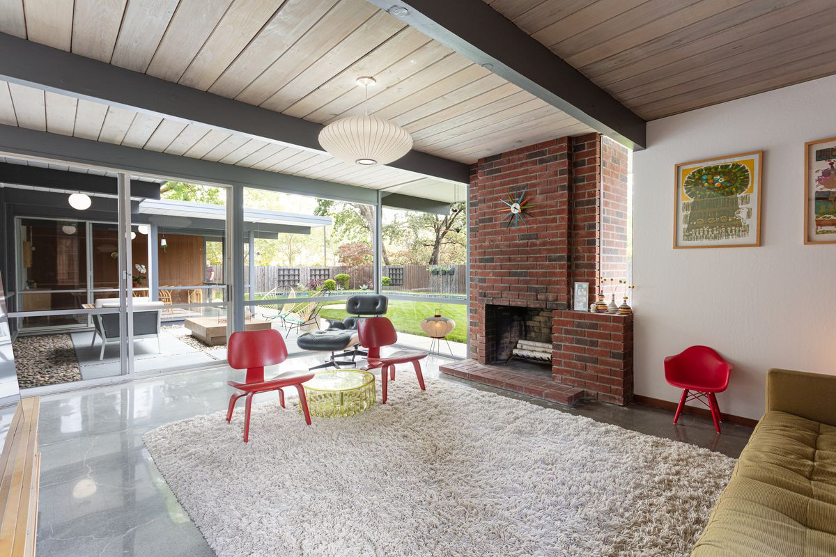 A living room with a red brick fireplace a white shag run on top of a gleaming concrete floor.