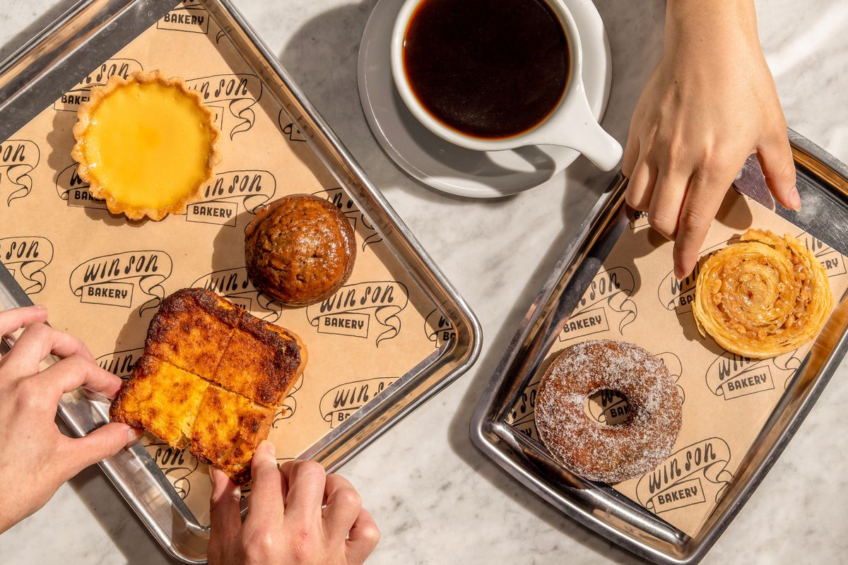 Assorted pastries, including mochi doughnuts and bright yellow custard toast, on two stainless steel trays alongside a cup of coffee, at Win Son Bakery