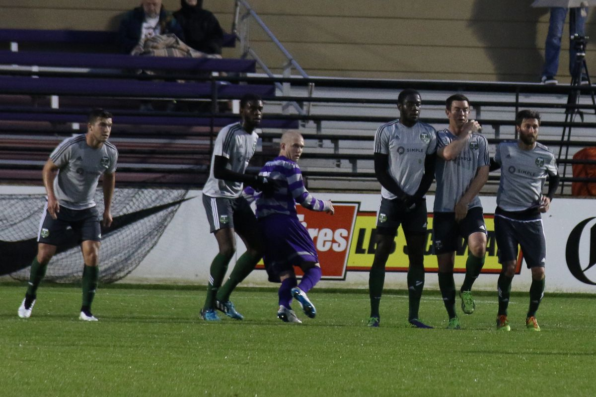 Clarke (center, defending) awaits a UP free kick on March 22, 2015