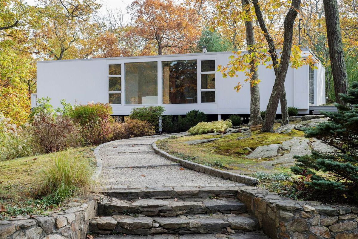 Exterior shot of white box with large floor-to-ceiling window on low stilts on rocky site surrounded by trees.