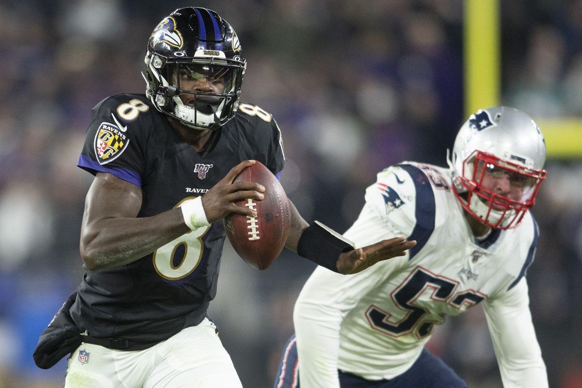 Baltimore Ravens quarterback Lamar Jackson runs past New England Patriots linebacker Kyle Van Noy during the fourth quarter at M&T Bank Stadium.
