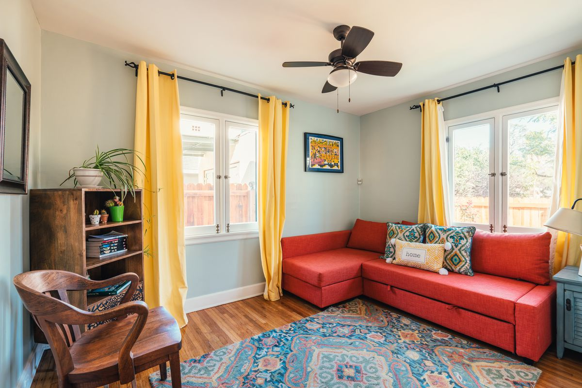A room with a sofa and bookshelf.