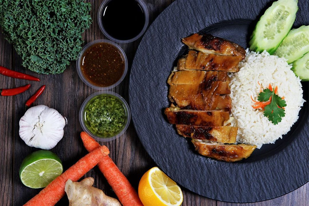 Overhead view of Hainanese chicken rice with a variety of sauces and ingredients next to the plate.